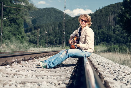 rips: Smiling young man with guitar sitting on the railway