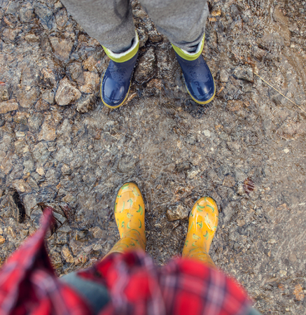 gumboots: Two pairs legs in colorful gumboots Stock Photo