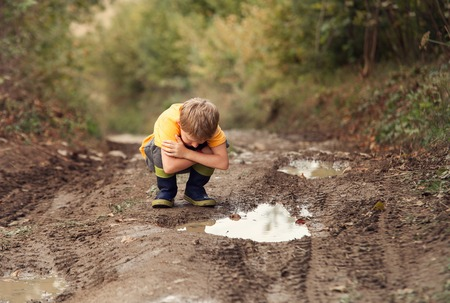 Boy look into the puddle on the country road Banque d'images