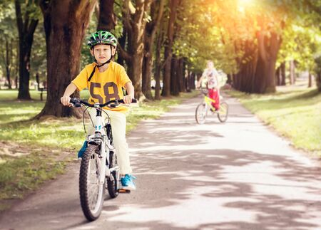 two boys: Two boys ride a bicycle in park