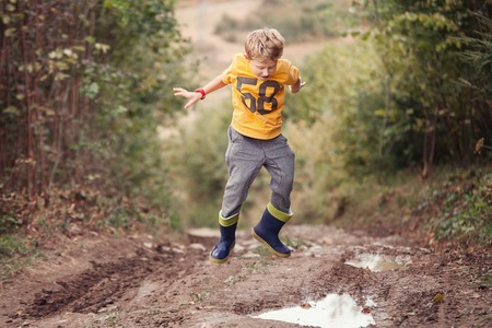 dirt road: Boy in gumboots jumps into the puddle Stock Photo