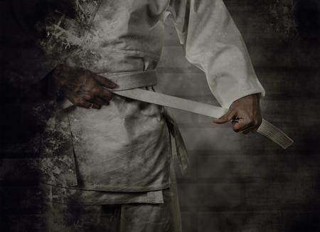 Karateka tying the white belt (obi) with grunge background