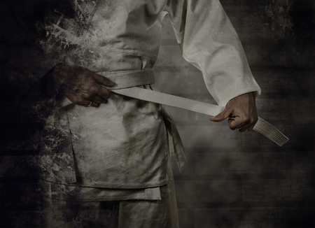 Karateka legando la cintura bianca (obi) con sfondo grunge Archivio Fotografico - 46067250