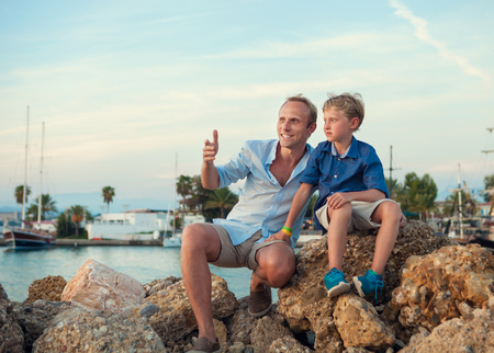 dad son: Father with son in tropical sea harbor on sunset time Stock Photo