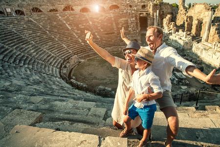 семья: Веселая семейка сфотографировать себя с друзьями в амфитеатре здания Фото со стока