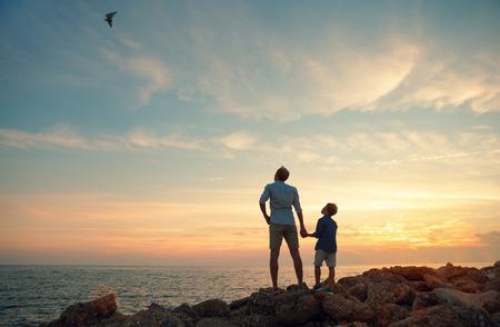 edad de piedra: Padre con el hijo en la costa del mar en la puesta del sol