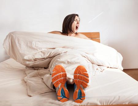 ウェイク アップあくびベッドに座って実行の靴の女の子