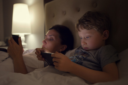 Mother with son lying in bed and look in their electronic device