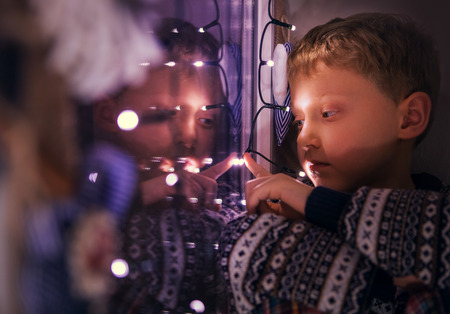 ni�os pensando: Primer retrato del muchacho que se sienta en la ventana con las luces de navidad