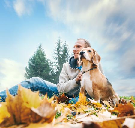 hombre cayendo: Hombre con beagle en el otoño de la opinión del paisaje Foto de archivo