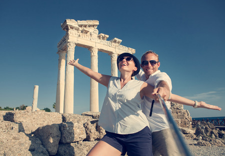 Happy young couple take a selfie photo on antique ruins. Temple of Apollo, Side, Turkey Фото со стока