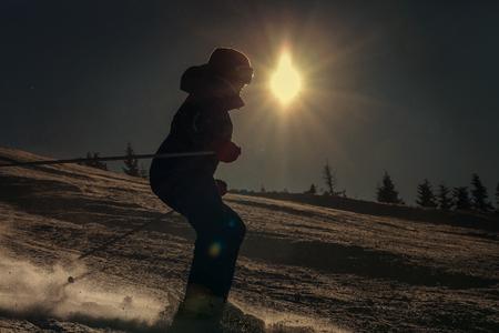 jumps: Girl skier skate down on snow hill in sun backlight Stock Photo