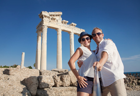 funny: Smiling young couple take a selfie photo on antique ruins. Temple of Apollo, Side, Turkey