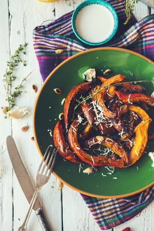 people eating: Roasted pumpkin with blue cheese, garlic and thyme Stock Photo