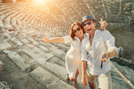 take a history: Happy young couple take self photo in Side amphitheatre