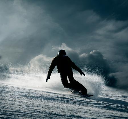 personas saltando: Snowboarder desliza por la colina de nieve