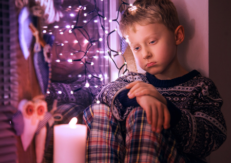 depression: Sad Little boy waiting for Christmas presents Stock Photo