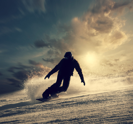 adventure travel: Snowboarder slides down the snowy hill Stock Photo