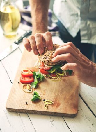 Man hands take a sandwich with ham and vegetables