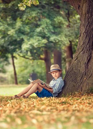 persona sentada: Muchacho con el libro sentado bajo el árbol grande en el parque