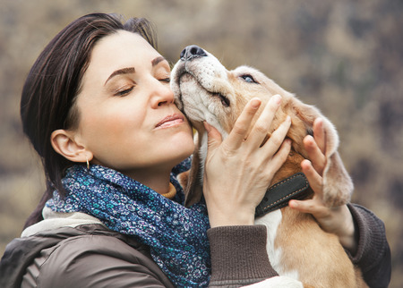 beagle puppy: Woman and dog tender hugs