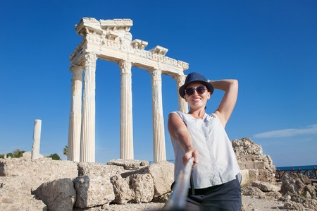 to post: Pretty young woman take a self photo on the antique temple view. Temple of Apollo,Side,Turkey Stock Photo
