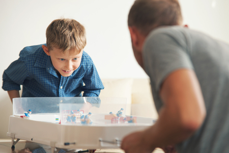 small table: Father with son enthusiastically playing with table hockey