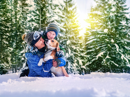 mothers: Mother with son and dog playing together in snow forest