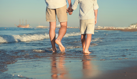 footprints in the sand: Father and son legs on the sea surfline close up image Stock Photo