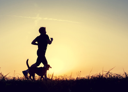 silueta humana: Tarde trotar caminar con un perro siluetas