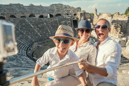 Young positive famly take a vacation photo on the Side ampitheatre view Stock Photo