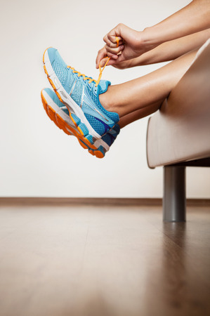 volition: Runner lace her run shoes sitting in bed Stock Photo