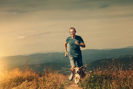 Man running with his dog on the mountain tableland Stock Photo
