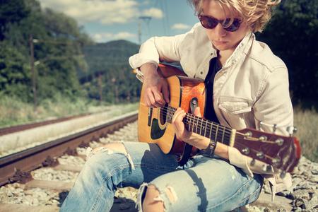 cabello rubio: Hombre joven que juega en la guitarra Foto de archivo