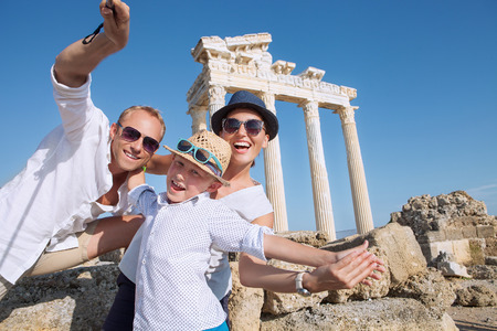 Positive young family take a sammer vacation selfie photo on antique sights view Standard-Bild