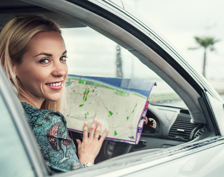 drive car: Pretty young woman sitting in car with a roads map