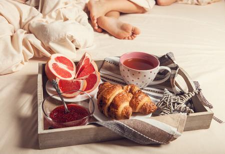Ontbijt met croissant op dienblad op het bed in de buurt van slapende persoon Stockfoto