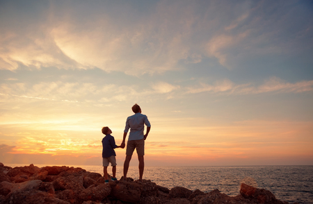 father and son: Father with son on the sea coast in sunset time