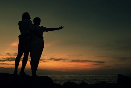 mujer mirando el horizonte: Inlove de los pares en la costa en el tiempo de la puesta del sol
