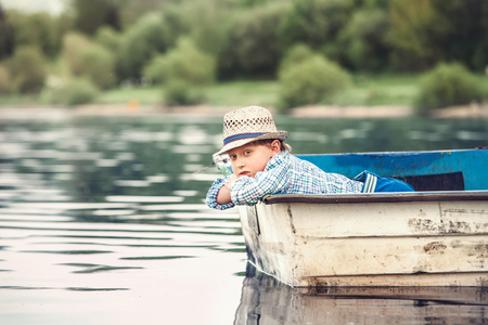 dream lake: Little boy lying in the old boat on a pond at the summer evening Stock Photo