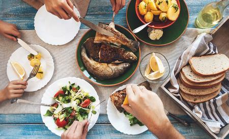 comiendo pan: cena familiar con pescado frito, patatas y ensalada