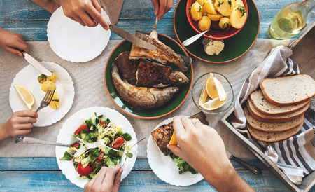 table: Family dinner with fried fish, potato and salad