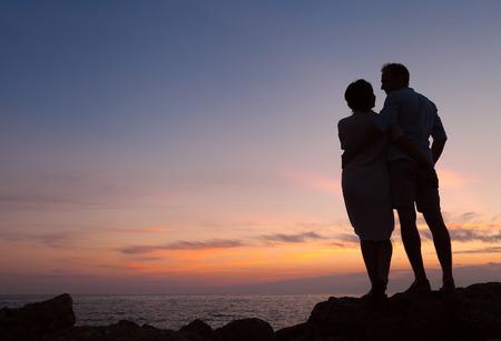 mujer mirando el horizonte: Amante de la pareja puesta de sol silueta Foto de archivo
