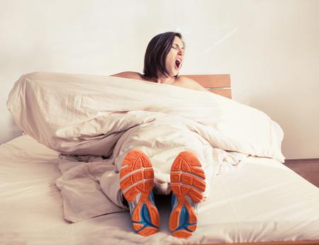 Wakker gapende meisje in run schoenen zitten in bed Stockfoto