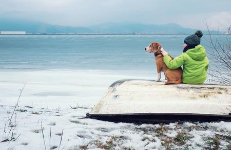 犬は冬の湖の近くの古いボートに一緒に座っている少年