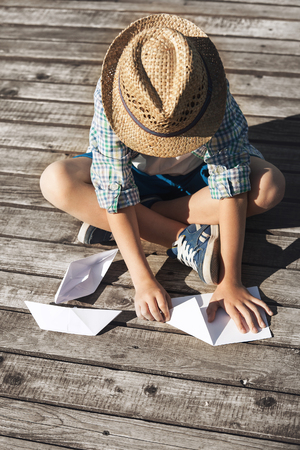 making fun: Boy making a paper boats on the wooden pier Stock Photo