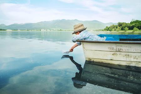 湖の古い船から小さな少年発売紙船します。