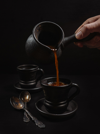 Hombres mano vertiendo el café en la taza de arcilla: negro sobre el negro