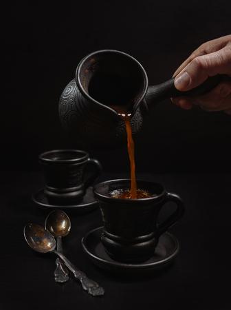 Mannen hand gieten van de koffie in klei kop: zwart op de zwarte