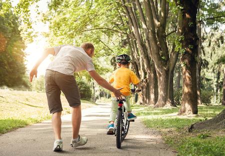 niños en bicicleta: Padre aprender a su pequeño hijo a andar en bicicleta